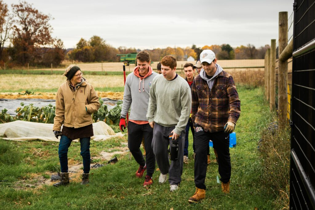 Farmer Lisa works with fraternity brothers to build our first mini high tunnel.